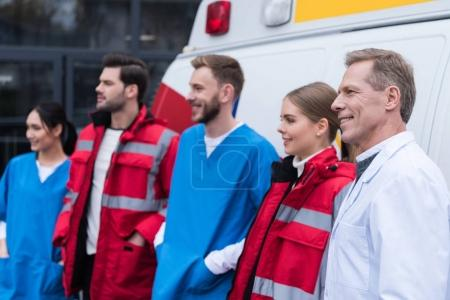 ambulance doctors working team smiling and standing in front of car