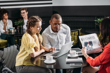 young successful business partners looking at laptop together