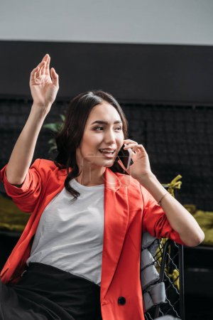 young asian woman talking by phone and waving hand