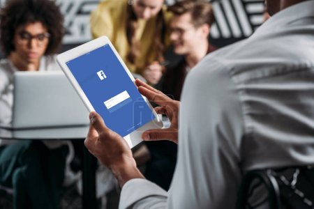 man using tablet with facebook app on screen with his business partners on background