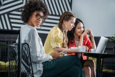 group of multiethnic businesswomen working together in cafe
