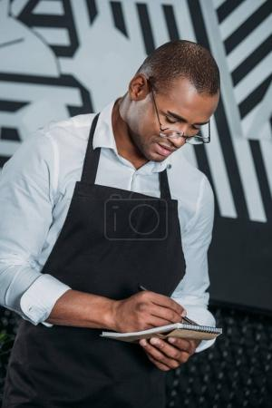 handsome young african american waiter writing in notepad