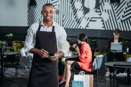 Photo for Handsome young waiter in apron standing at cafe - Royalty Free Image