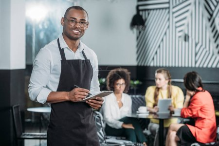 happy young waiter writing in notepad with multiethnic group of women sitting blurred on background