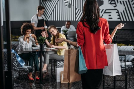 woman with shopping bags going to her friends in cafe
