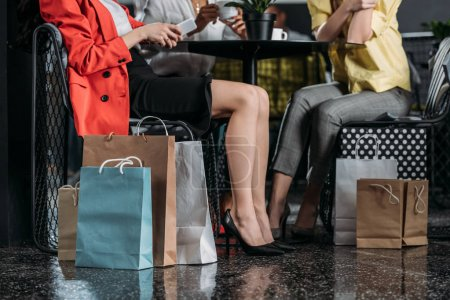 cropped shot of women with shopping bags sitting at cafe