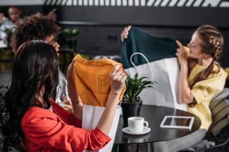 Photo pour Jeunes femmes montrant leurs nouvelles robes les uns aux autres après le shopping - image libre de droit