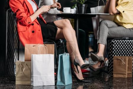 Photo pour Plan recadré de femmes élégantes avec des sacs à provisions assis au café - image libre de droit