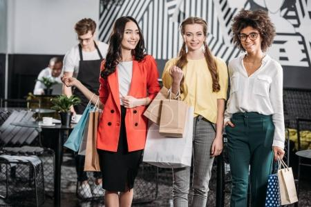 group of beautiful young women with shopping bags in cafe