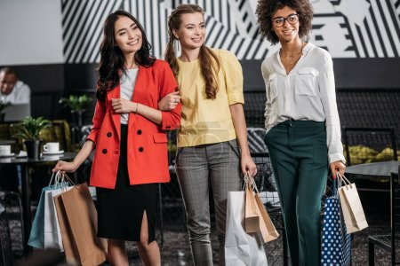 group of beautiful multiethnic women with shopping bags