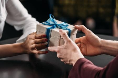cropped shot of man giving anniversary gift to girlfriend