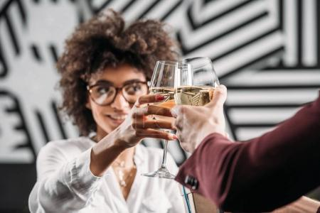 young african american woman clinking glasses of wine with boyfriend