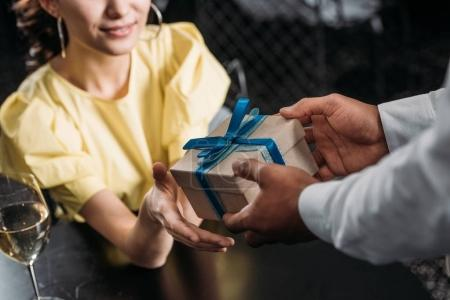 cropped shot of beautiful woman taking gift from boyfriend