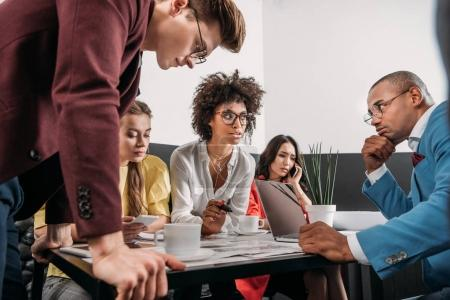 group of young business partners having conversation in cafe