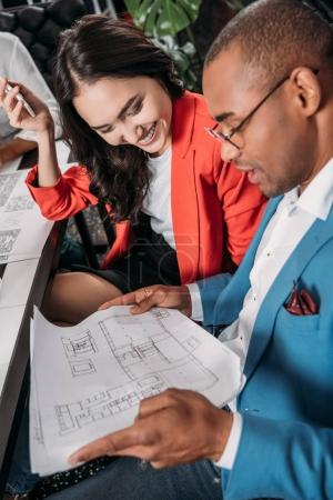 young business partners looking at building plan