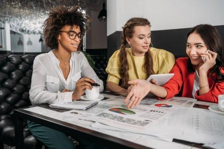 group of young businesswomen doing paperwork together