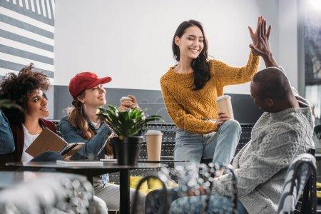 Foto de Grupo de jóvenes amigos, pasar tiempo en la cafetería y dando cinco alta - Imagen libre de derechos