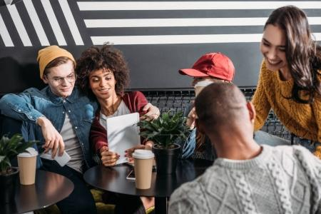 group of young friends spending time together in cafe