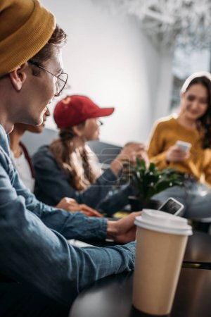group of young stylish friends spending time in cafe