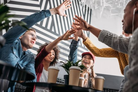 bottom view of friends giving high five in cafe