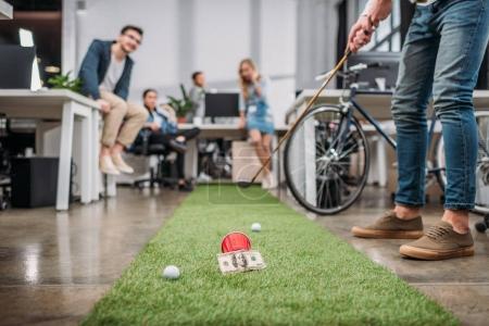Photo pour Image recadrée de personnes jouant au mini golf au bureau moderne - image libre de droit