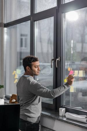 young man making notes on stickers at window