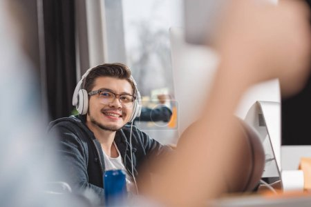 young man in headphones at modern office