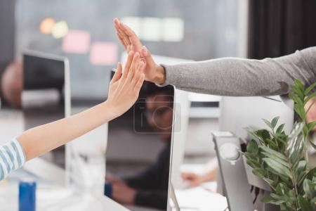 cropped image of hands giving high five to each other at modern office