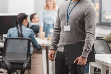 cropped image of african american with name tag and planchette at modern office