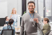 happy african american man showing name tag at modern office