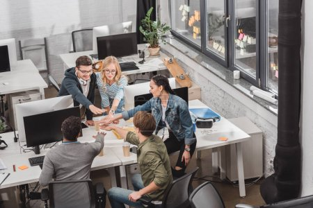 cheerful multicultural business team making stack of hands at modern office