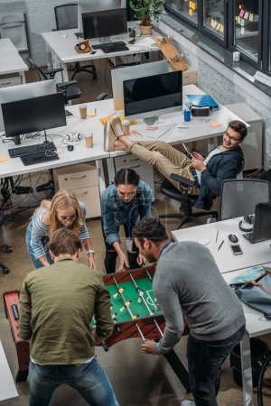 multicultural people playing in table soccer at modern office