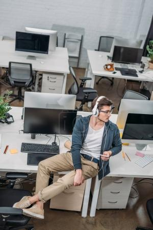 young man listening music in empty modern office