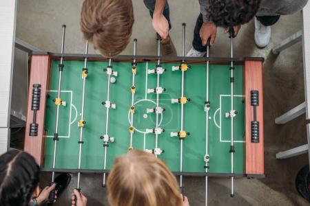 top view of cropped multicultural people playing in table soccer at modern office