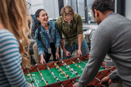 happy multicultural people playing in table soccer at modern office