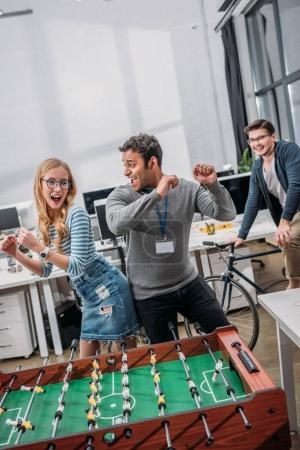 happy man and woman celebrating victory in table soccer at modern office