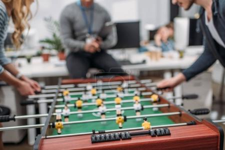 cropped image of people playing in table soccer at modern office