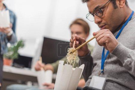 african american man eating thai food at modern office