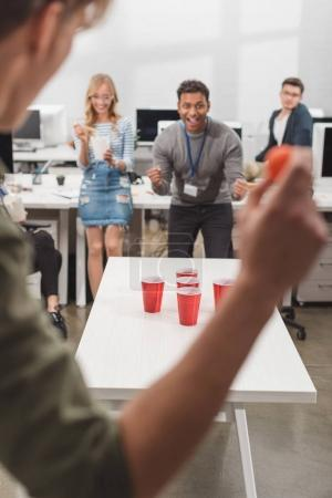 excited people playing beer pong at modern office after work