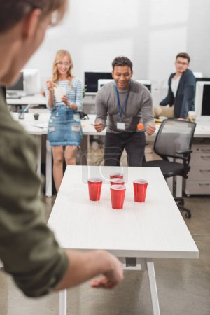young attractive people playing beer pong at modern office after work