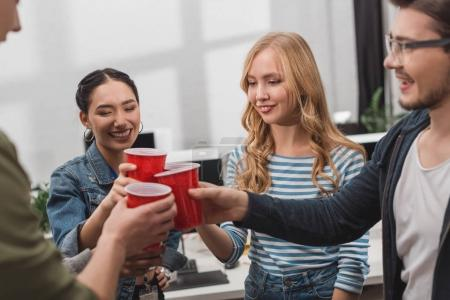young attractive people clinking cups at modern office