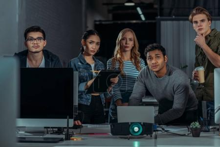young people watching presentation in modern office and writing something