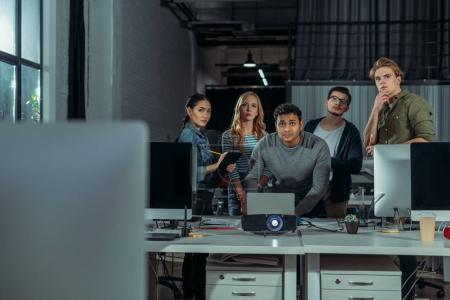 young people watching presentation in modern office at nighttime