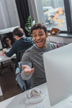 excited man reaching hand at modern office