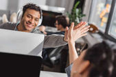 man and woman giving high five to each other at modern office