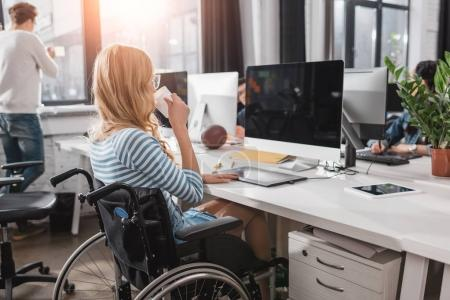 incapacitated person in wheelchair working at modern office