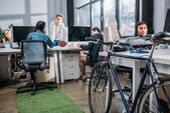 """Постер, картина, фотообои """"Различные люди, работающие в современном офисе с велосипедов"""""""