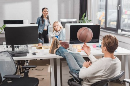 women watching at man spinning ball at office