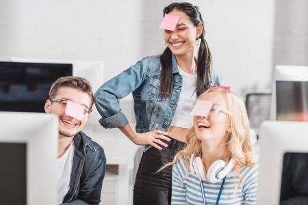 Photo for Happy people with stickers on heads at modern office - Royalty Free Image
