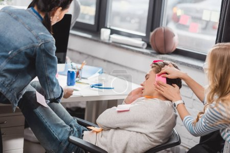 women glue stickers on sleeping man at office